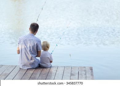 Dad and son fishing on a pier