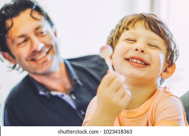 Dad and son having fun together on bed at home - happy family of a child laughing with lollipop in the living room with his father - Concept of unity, childhood and love