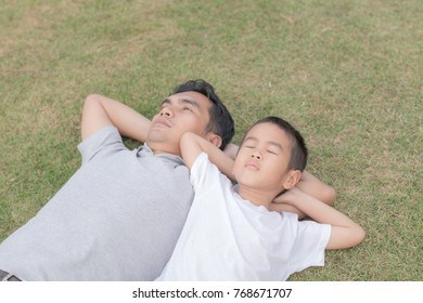 Dad and son lie on the lawn in the garden