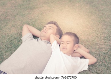 Dad and son lie on the lawn in the garden at the evening with vintage color tone