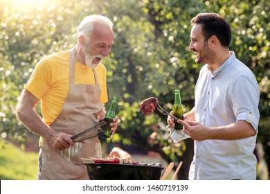 Papa und Sohn machen Grill und trinken Bier im Garten.