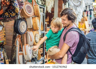 Dad and son at a market in Ubud, Bali. Typical souvenir shop selling souvenirs and handicrafts of Bali at the famous Ubud Market, Indonesia. Balinese market. Souvenirs of wood and crafts of local