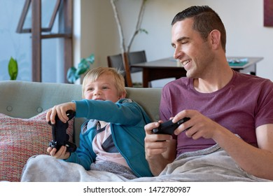 Dad and son on couch playing computer games with remote controllers having fun at home