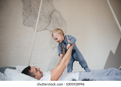 Dad and son in pajamas. Pajama party. Suspended bed. A room in Scandinavian style. Embrace and play. A little boy with blond hair.