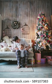 Dad and son in pajamas sitting on the couch at the Christmas tree