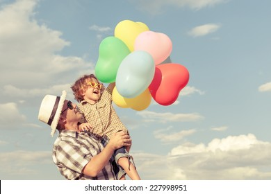 Dad and son playing with balloons near a house at the day time