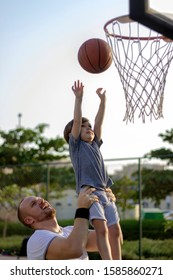 Dad and son playing basketball together.Father raised his son up in the air.Low angle image of son in his father's arms throwing a basketball into the hoop.Shot of happy family bonding.Copy space.