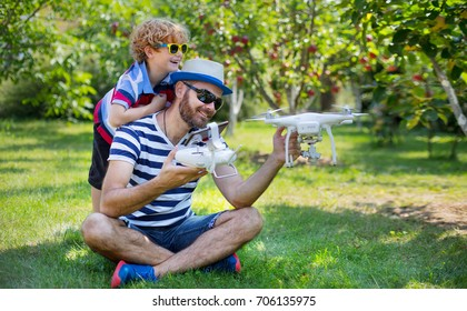 Dad and son playing with drone, man and boy playing with flying drone in sunny autumn garden, happy young boy and father playing with unmanned aerial vehicle (quadrocopter), spending time together.