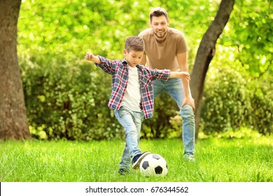 Dad and son playing football together on green meadow