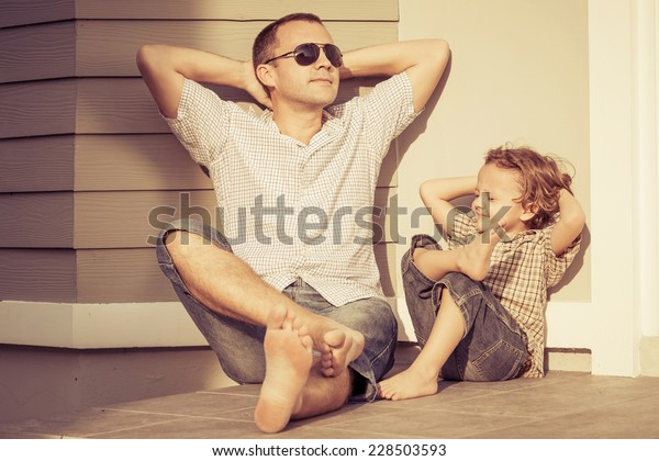 Dad and son playing near a house at the day time