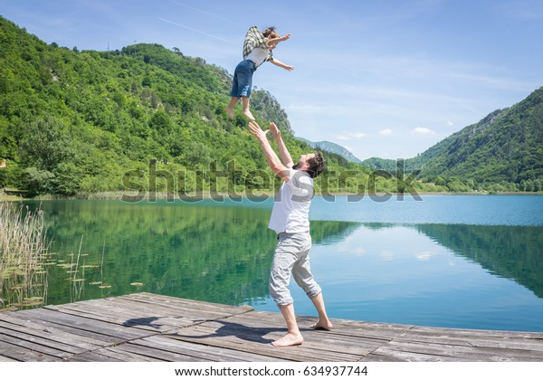 Dad and son playing on the mountain lake