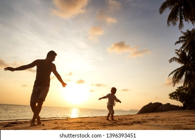dad and son playing on the sand at the beach at sunset