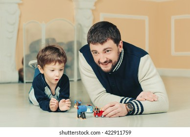 Dad and son playing with toys on a floor