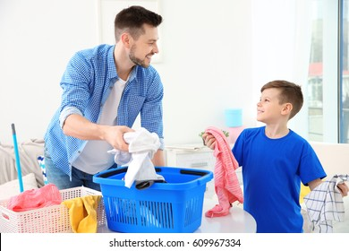 Dad and son preparing clothes for laundry at home