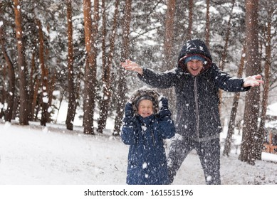 Dad and son rejoice in the falling snow in winter. A family is standing in the forest. There is a place for text on the left of the frame. Happy national snow day.