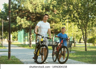 Dad and son riding bicycles in park on sunny day