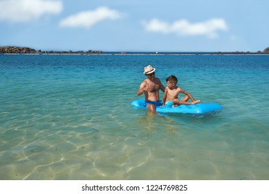 Dad and son are sitting on a blue inflatable floater in the clear ocean water. They are looking to each other, smiling, having fun and enjoying their vacations.