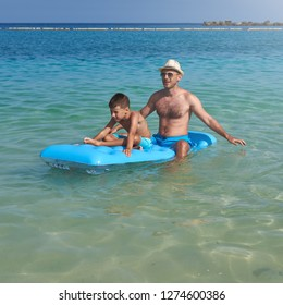 Dad and son are sitting on a blue inflatable floater in the clear ocean water. They are having fun and enjoying their vacations.