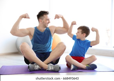 Dad and son sitting on floor and showing muscles indoors