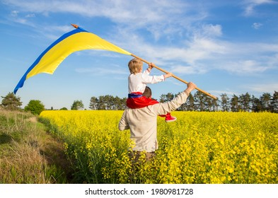 dad with son, sitting on his shoulders, in national Ukrainian clothes with large flag of Ukraine in hands against background of a blooming yellow rapeseed field. Patriotic education. Pride, freedom