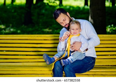 Dad and son are sitting on a yellow bench in the park and putting on ties. Father's Day.