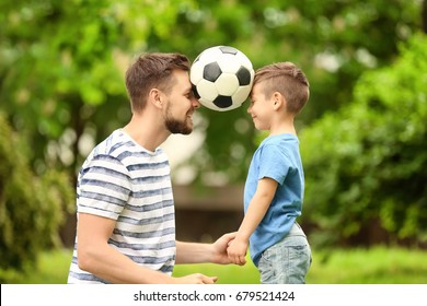 Dad and son with soccer ball in green park