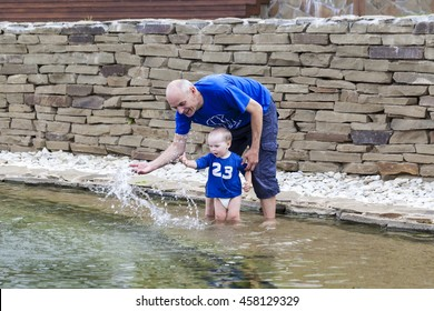 Dad with son splash of water in a pond