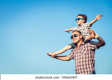 Dad and son in sunglasses playing in the park at the day time. People having fun outdoors.  Concept of friendly family.