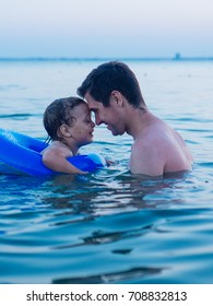 dad and son are swimming in the sea