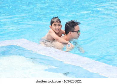 Dad and son are swimming together in the summer.