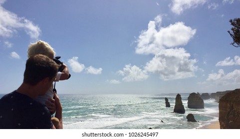 Dad and son take photograph of Twelve Apostels