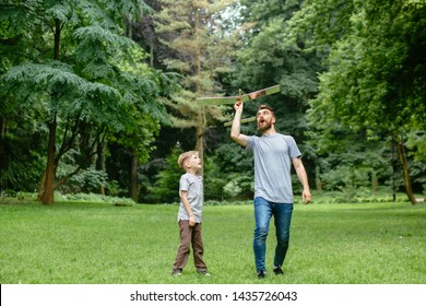 Dad and son together launch model airplane outdoors, both man and boy are looking cheerfully at plane. Father and son spending good time together, family relationships concept. Full leight
