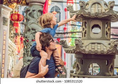Dad and son are tourists on the Street in the Portugese style Romani in Phuket Town. Also called Chinatown or the old town. Traveling with children concept