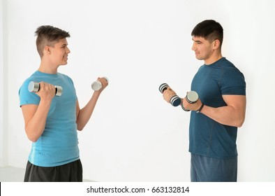Dad and son training with dumbbells in gym