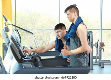 Dad and son training on treadmills in modern gym