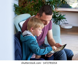Dad and son using technology at home, using electronic tablet device solving puzzles playing games modern lifestyle