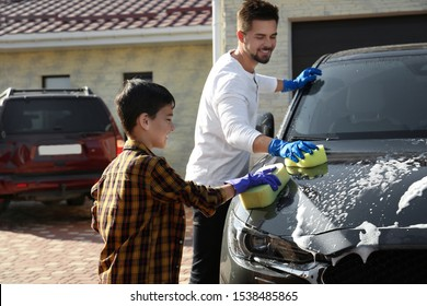 Dad and son washing car at backyard on sunny day