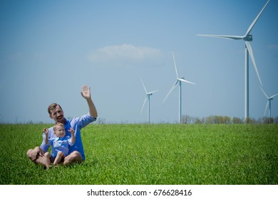 Dad and son waving their hand to wind generators sitting on the field
