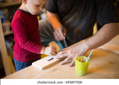 Dad and son work in a furniture workshop. A little boy makes a toy out of wood