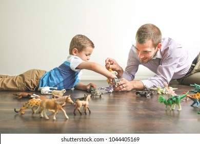 Dad spending quality time with toddler son playing with animal figures