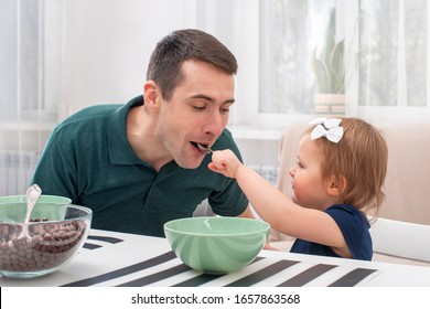 Dad take care of a little daughter at home.  He gave her cereal with milk.  The modern role of men in the family.