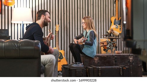 Dad teaching guitar and ukulele to his daughter.Little girl learning guitar at home.Side view.Ukulele class at home. Child learning guitar from her father