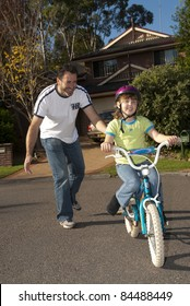 Dad teaching his daughter to ride a bike