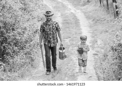 Dad teaching son care plants. Arbor day. Planting trees. Tree planting tradition. Little helper in garden. Planting flowers. Growing plants. Boy and father in nature with watering can and shovel.