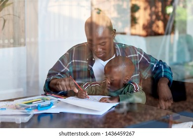 Dad teaching son how to draw, candid moment family at home spending quality time together