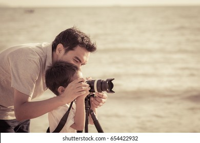 Dad is teaching son taking a photo at the beach at sunset with vintage color tone