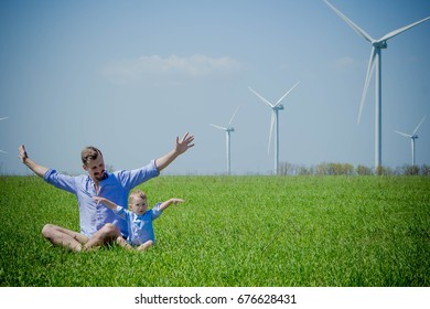 Dad tells his young son about alternative sources of energy sitting on the field with wind generators