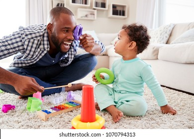 Dad and toddler son having fun playing at home, close up