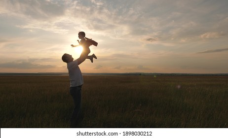 Dad tosses his happy daughter into blue sky. Daddy and a small child play together on field, laugh and hug. Family travel. Child is in arms of parent. Father day off. Happy family and childhood