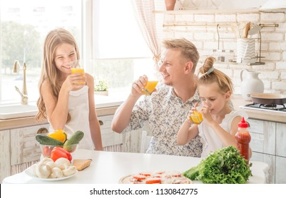 Dad with two daughters drinks orange juice in the kitchen